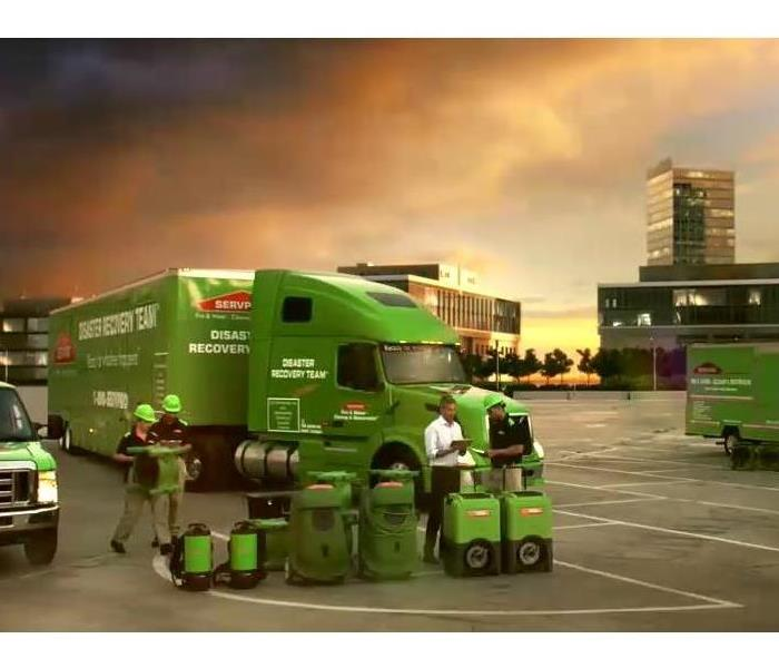 A fleet of SERVPRO vehicles in front of a smokey sky